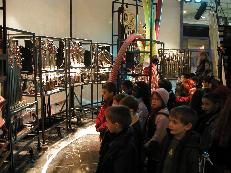 Photographie montrant groupe d'enfants devant machines en arc de cercle