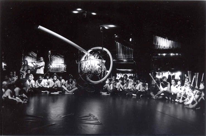Photographie en noir et blanc : sur une scène de spectacle, enfants assis en tailleur devant machines musicales
