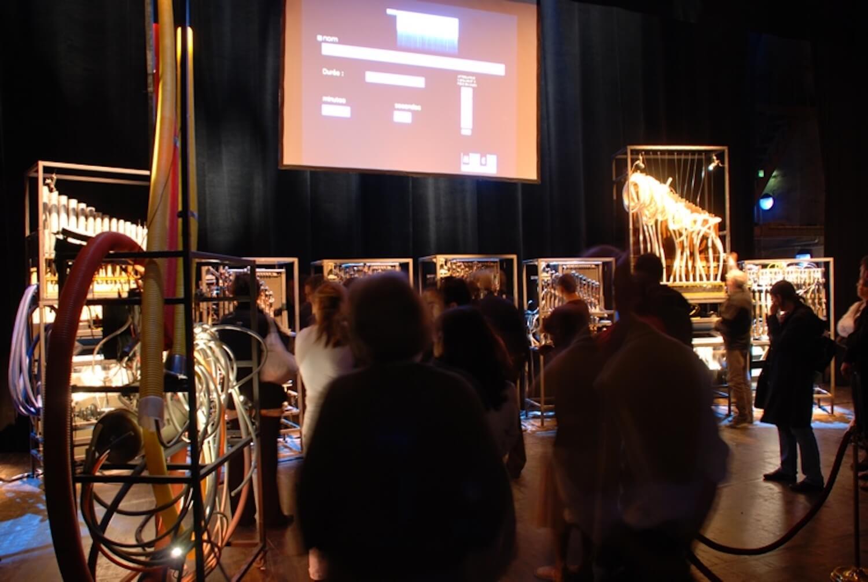 Photographie montrant public devant machine et écran, en lumière orange