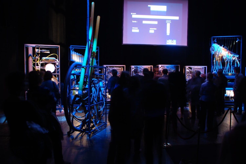 Photographie montrant public devant machine et écran, en lumière bleue