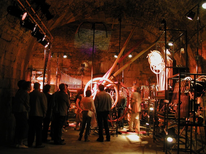 Photographie : public regardant des machines musicales dans une grande cave voutée, lumière orange-rouge