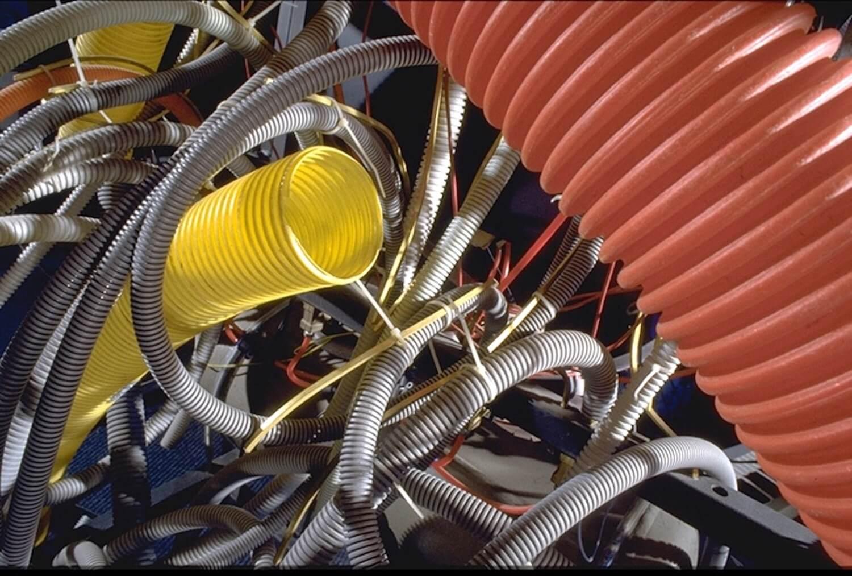 Photographie tuyaux plastique gris, rouge et jaune, emmélés