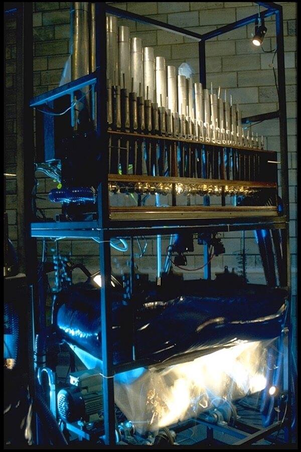 Photographie machines en mouvement avec tuyaux d'orgue au dessus, lumière bleue