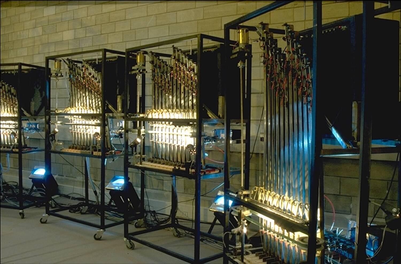 Photographie : 4 machines en cage avec barres verticales, support mobiles de cordes devant archets rotatifs