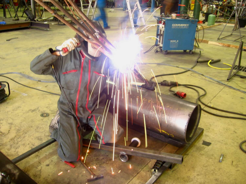 Photographie : une personne masquée effectue une soudure à l'arc sur une structure surplombant une gros tune métallique