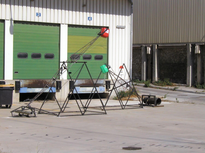 Photographie de 2 grands mécanismes à balancier en extérieur devant deux grandes portes vertes