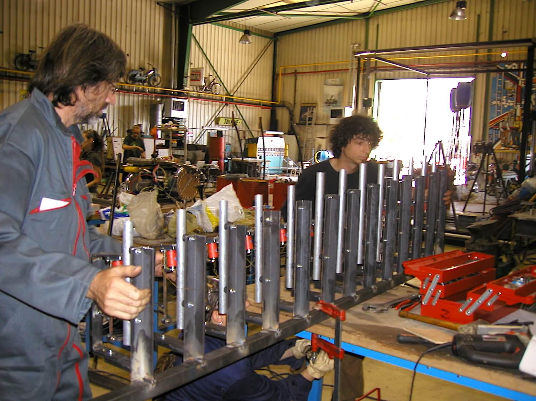 Photographie : un homme tient avec un jeune homme un ensemble formé de tubes en aluminium tenus sur des supports en acier