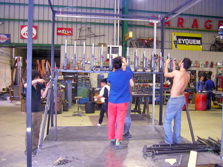 Photographie : 4 stagiaires assemblent des structures métalliques qui encadrent un montage de tubes de carillon avec électro-aimants
