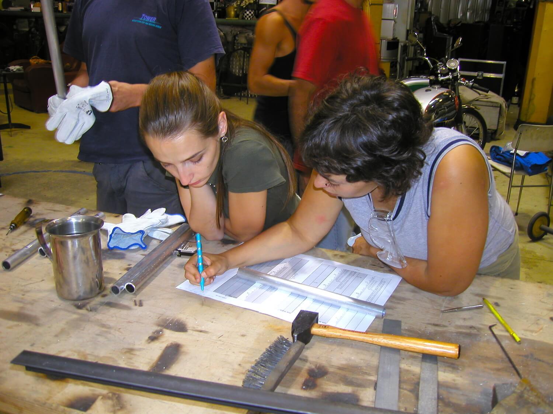 Photographie : 2 stagiaires tracent les plants des construction sur un table