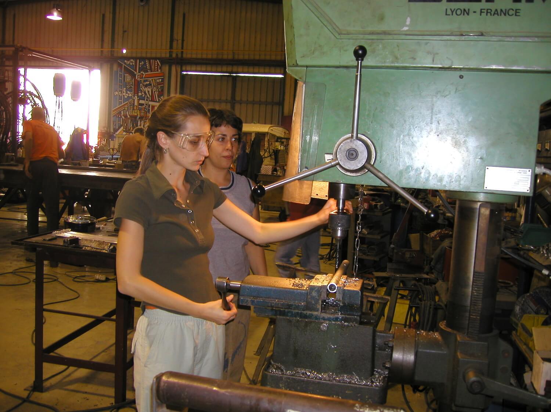 Photographie : 2 jeunes filles dont une manipule une perceuse industrielle dans un atelier