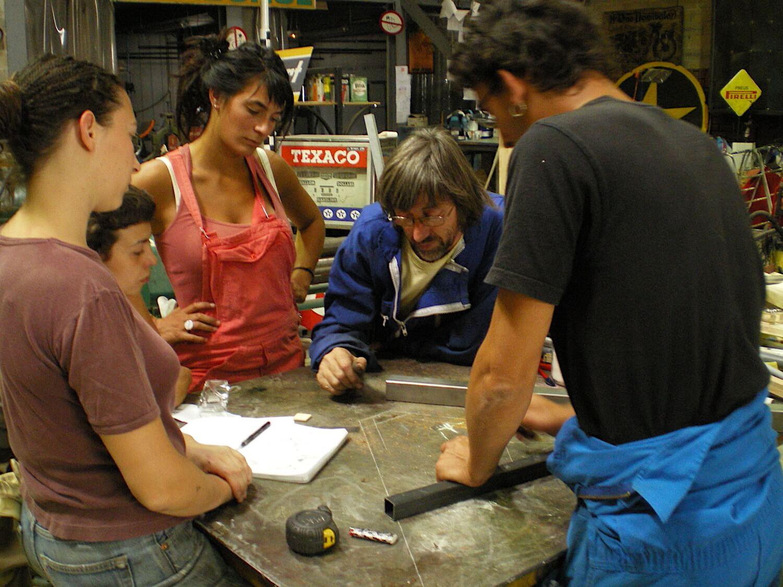 Photographie : 4 stagiaires entourent un homme en combinaison bleue qui trace des mesures sur une table mérttallique avec un tube carré