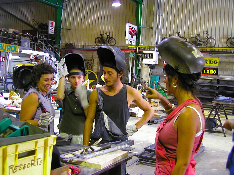 Photographie : 4 jeunes gens avec masque soudure à l'arc devant des éléments de métal sur une table.