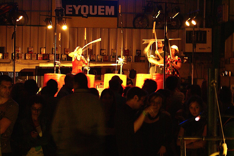Photographie : public devant 4 futs de 200 litres rouges transformés en contrebasse avec 3 interprètes tenant un archet