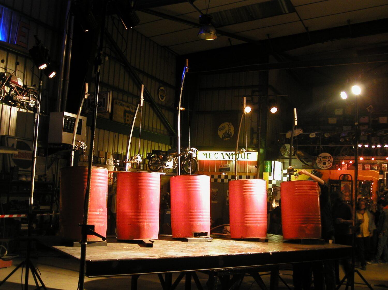 Photographie de 5 fûts de 200 litres transformés en contrebasses monocordes à moteur sur scène avec en fond un panneau lumineux «MÉCANIQUE»