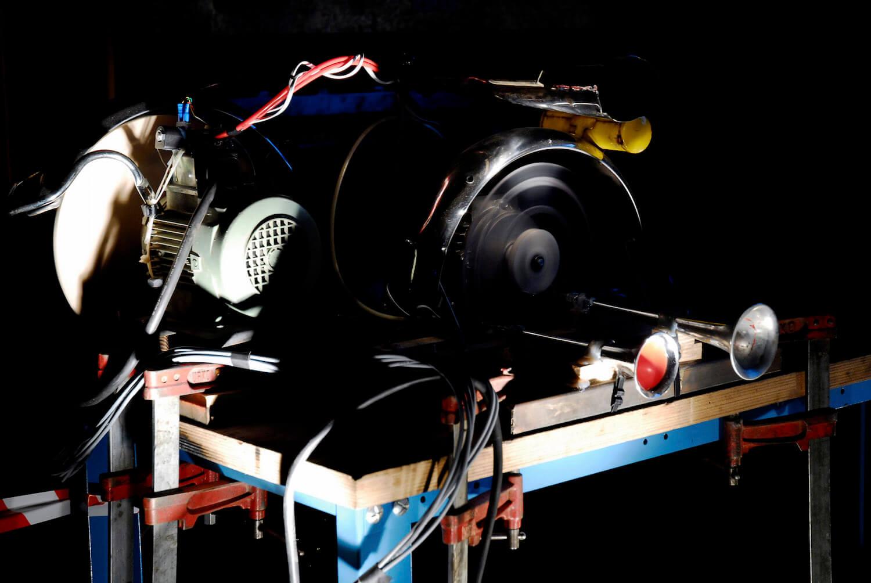 Photographie sur fond noir montrant moteur en rotation et 2 trompes de camion