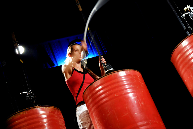 Photographie : 3 fut de 200 litres rouges avec jeune fille en rouge tenant un archet