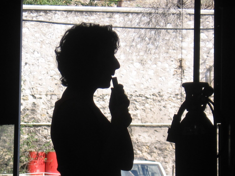 Photographie : profil comme une ombre chinoise , jeune femme souffle dans un petit tuyau