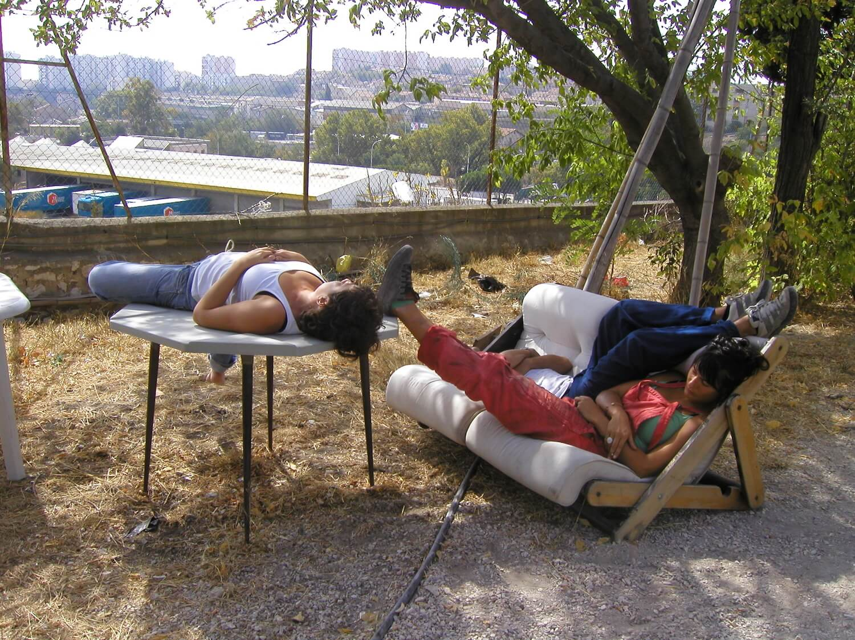 Photographie : 3 stagiaires font la sieste, écroulés sur une table et un canapé trop petit à l'ombre d'un arbre.