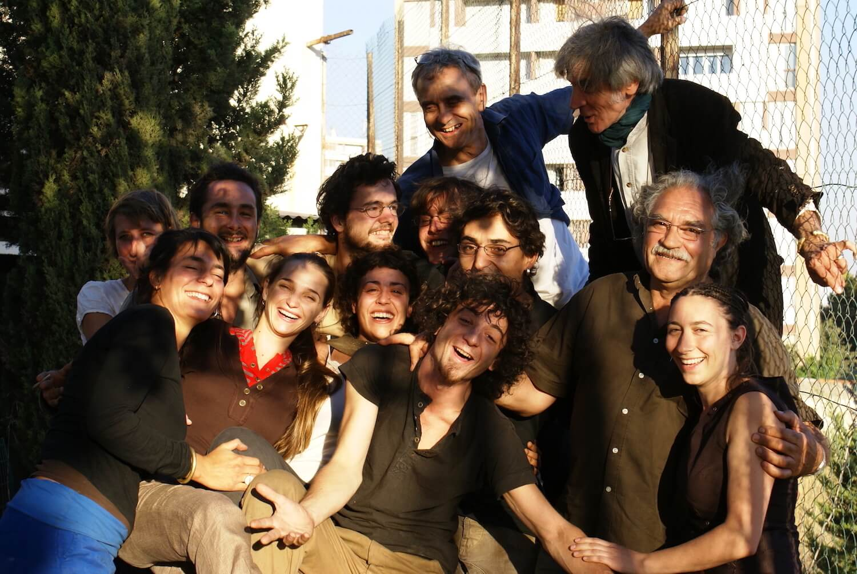 Photographie : une douzaine de personnes serrèes les uns contre les autres sourient au photographe