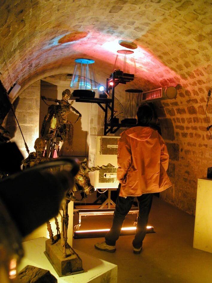 Potographie dans une cave vourée éclairée un peti refrigérateur est surmonté de 3 manèges de petuts carilons tubulaires qui tournent devant le public