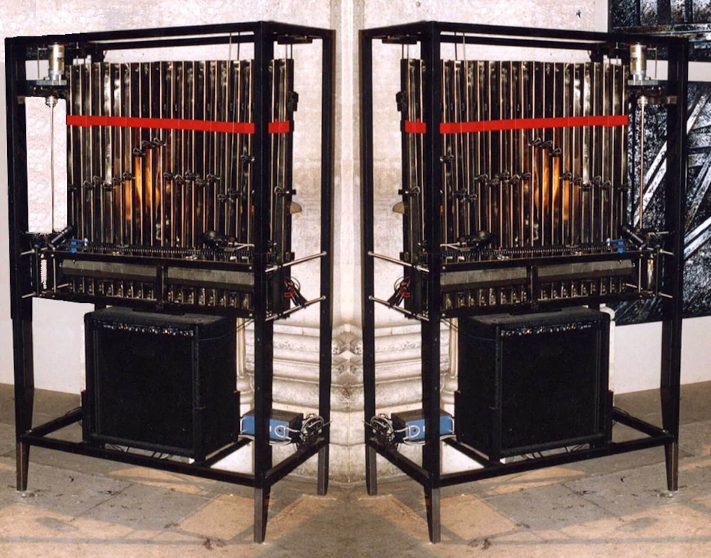 Photographie : 2 cages métalliques portent des barres verticales, un moteur et un haut-parleur de guitare