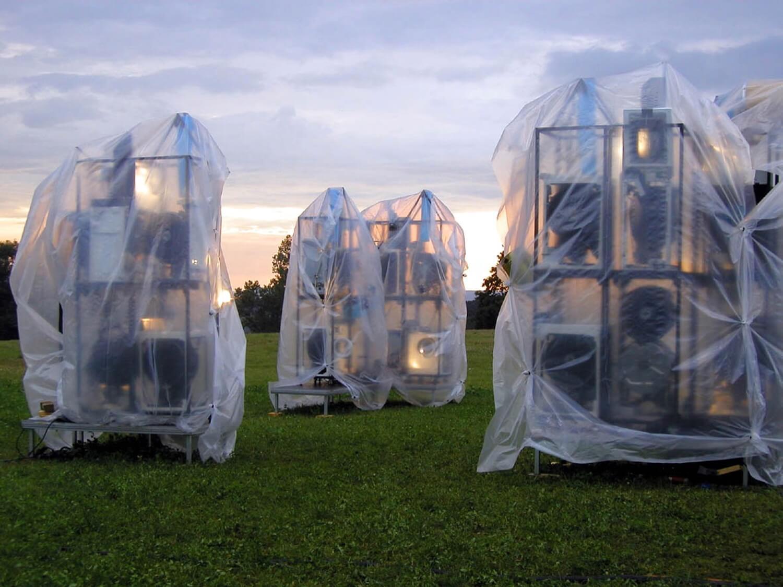 Photographie 3 groupes de structures métalliques contenant des machines sous bâches transparentes sur une pelouse avec lumière soleil levant