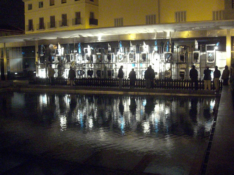 Photographie de nuit, devant un bassin d'eau public et mur de machines très éclairées
