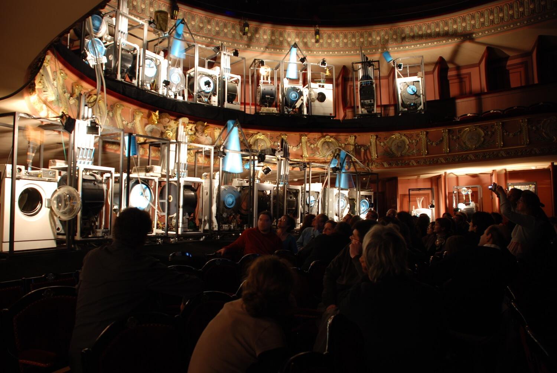 Photographie public regardant les machines éclairées dans les balcons d'un théâtre à l'italienne