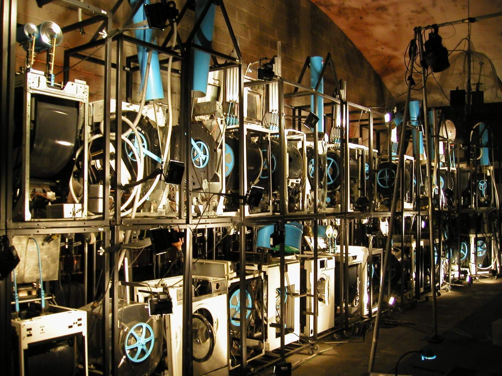 Photographie ensemble de machines à laver en cage, désossées, avec instruments de musique entrainés par leurs tambours