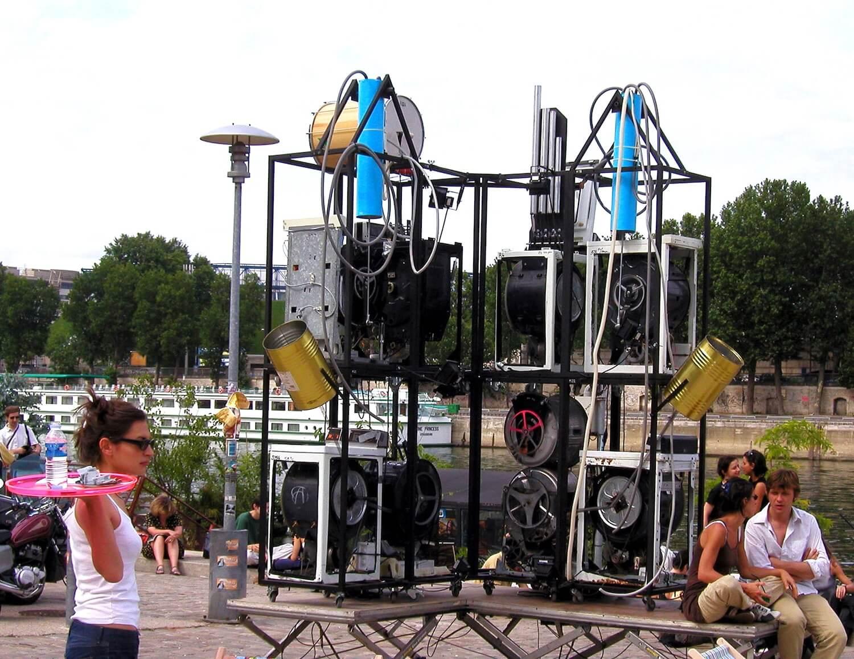 Photographie : un bloc de machines à laver avec instrument de musique au bord de la Seine avec public et jeune serveuse avec plateau rose en premier plan à gauche