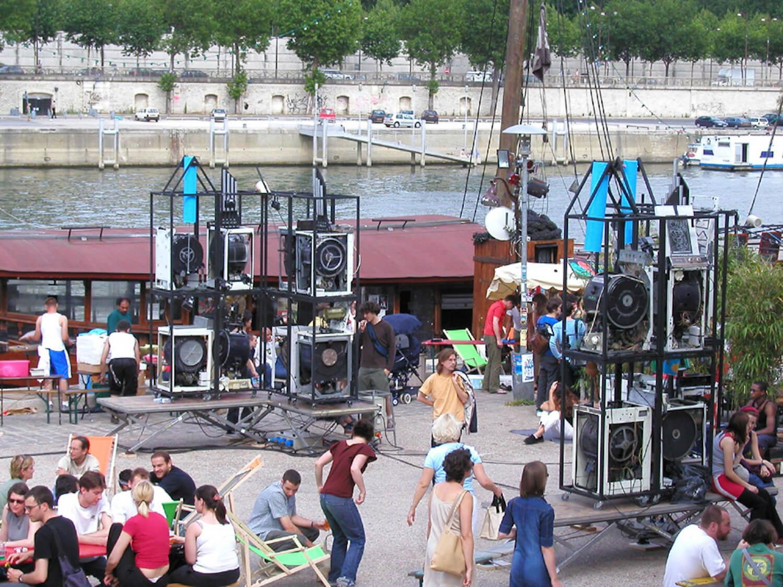 Photographie sur un quai au bord de la Seine, 2 ensembles de machines empilées en coin avec public autour
