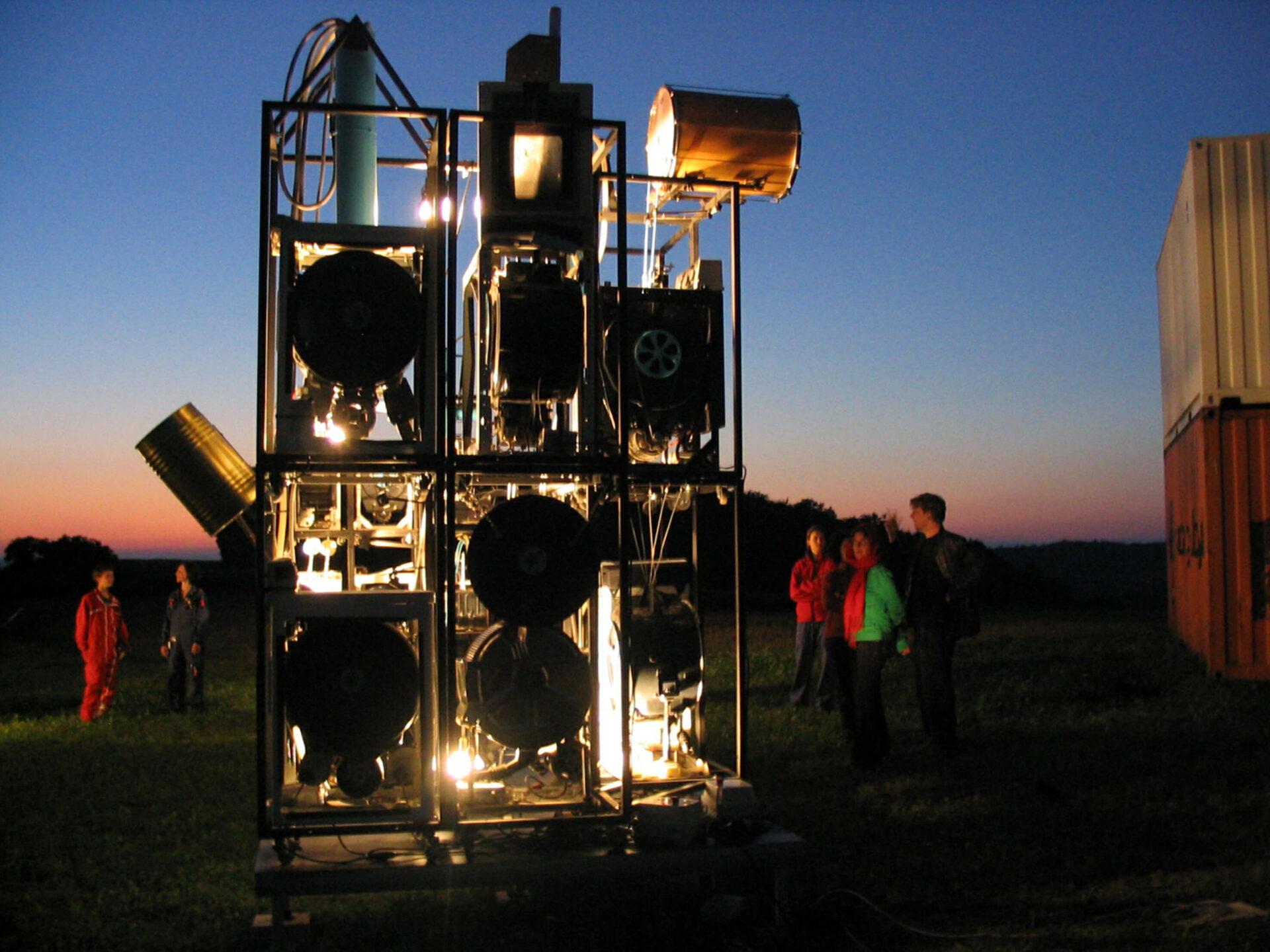 Photographie d'un groupes de structures métalliques contenant des machines entouré par le public, sur une pelouse, soleil couchant