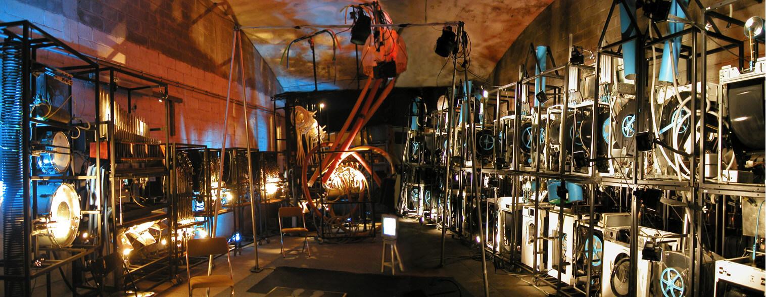 Photographie panoramique nombreuses machines musicales dans une immense cave voutée