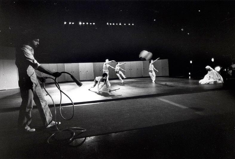 Photographie noir et blanc avec un musicien joueur de trompe et au fond 5 danseurs