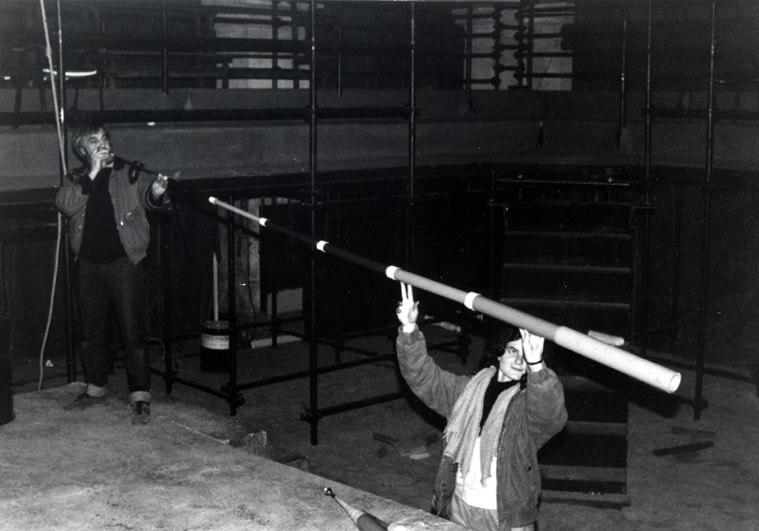Photographie Noir et Blanc un homme souffle dans une trompe de plusieurs mètres tenue par une deuxième personne