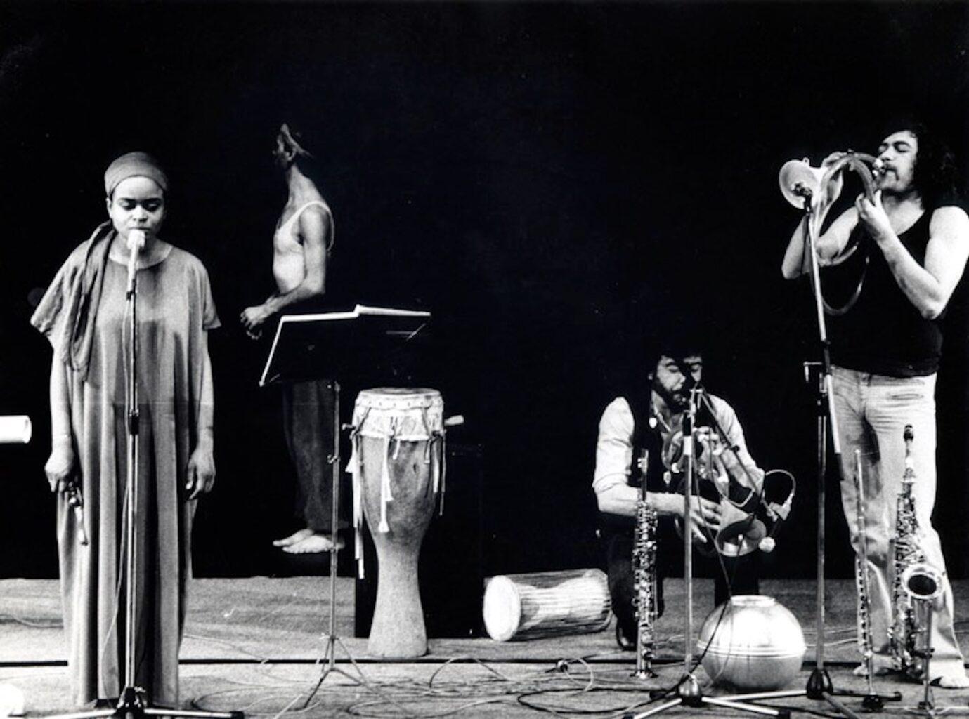 Photographie noir et blanc avec une chanteuse, un saxophoniste et un joueur de trope et au fond un danseur