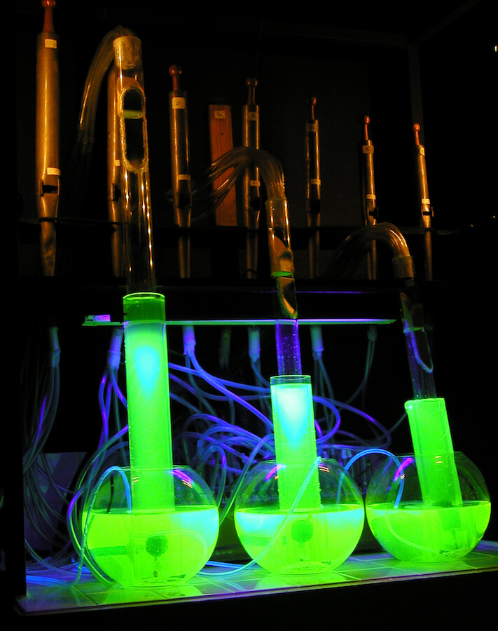 Photographie : 3 tubes en verre avec liquide phosphorescent vert plongent dans 3 bonbonnes remplies du même liquide sur fond de tuyaux d'un petit orgue