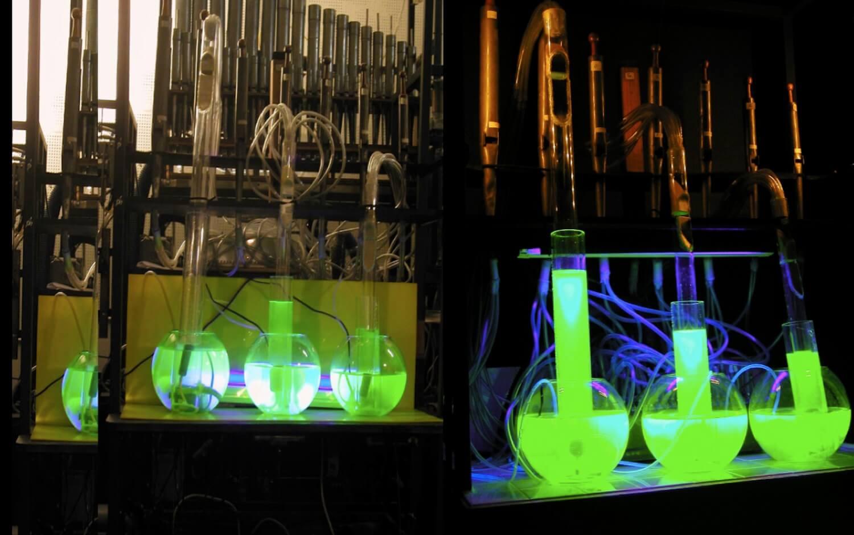 Deux photographies de 3 tubes transparents plongeant dans 3 sphères remplies de liquide phosphorescent montant dans les tube, devant des jeux d'orgue traditionnels