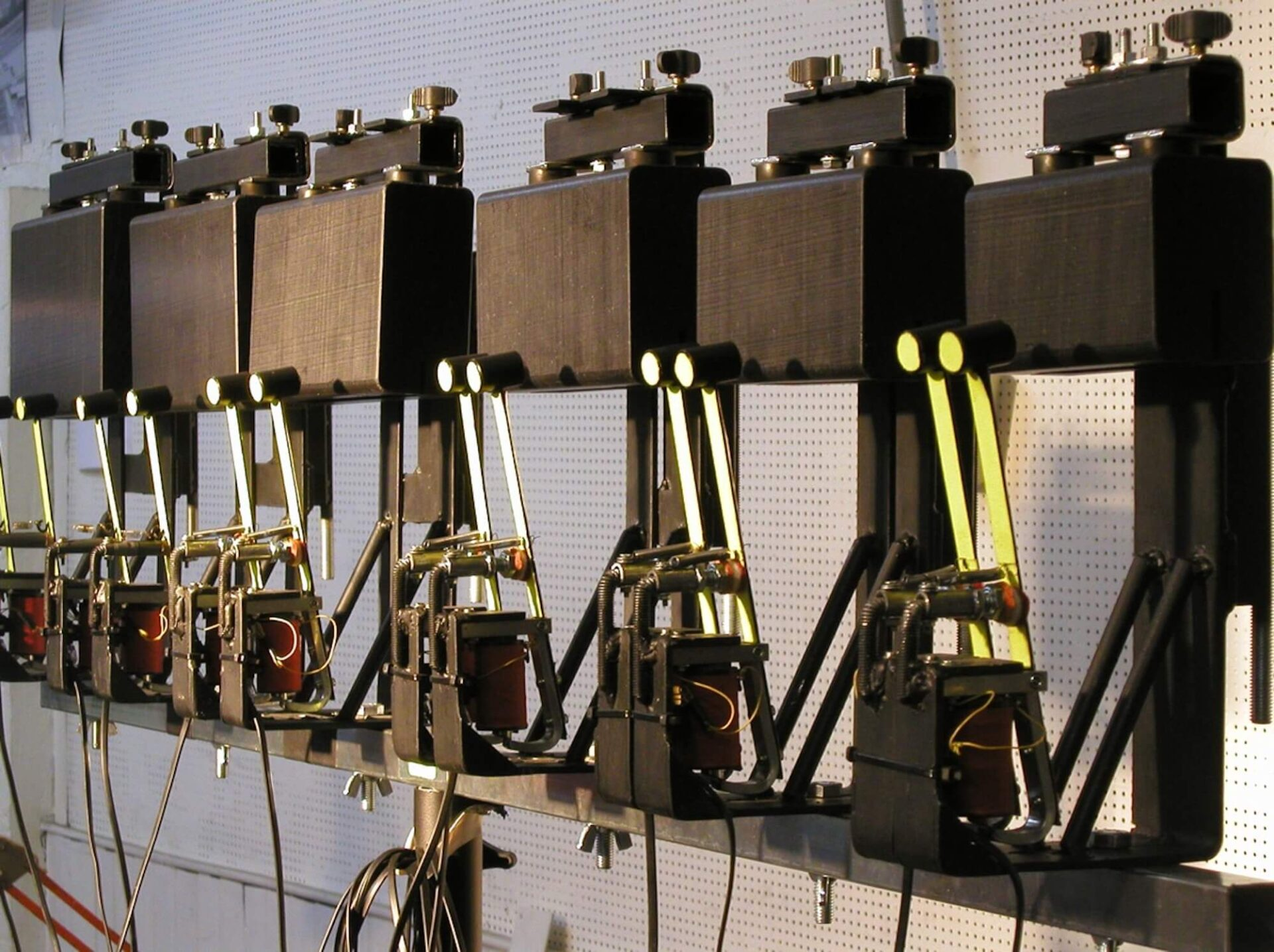 Photographie montrant 6 blocs noirs percutés par baquejjes jaunes alimentés par electro-aimants