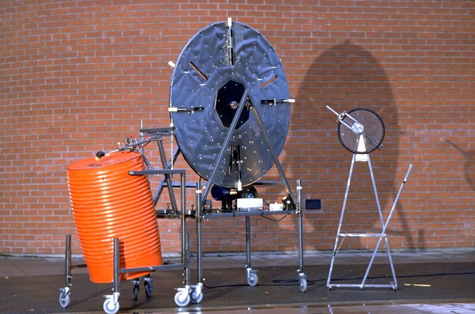 Photographie : tambour rouge-orange (fut de 200litres), frappé par des baguettes mises en oeuvre par une très grande toue métallique à programme et sa télécommande.