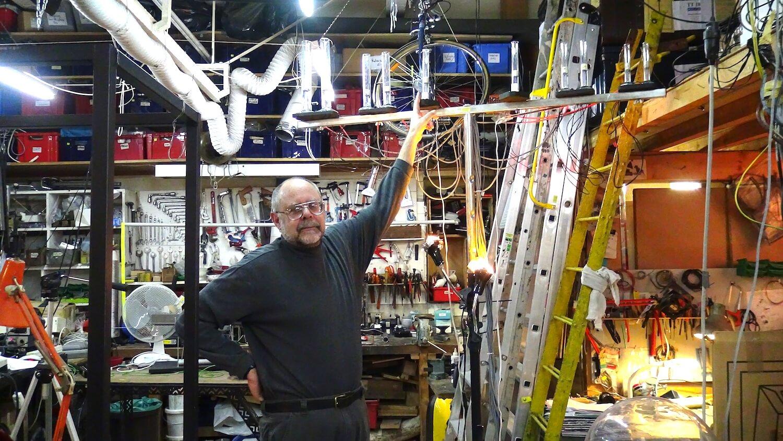 Phtographie , un homme avec lunettes montre un tube à essai muni de fils electriques dans le cadre d'un atelier