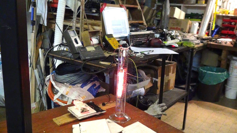 Photographie : un tube en verre avec une forte lumière jaune orange à l'intérieur dans un atelier avec banc de mesure electronique