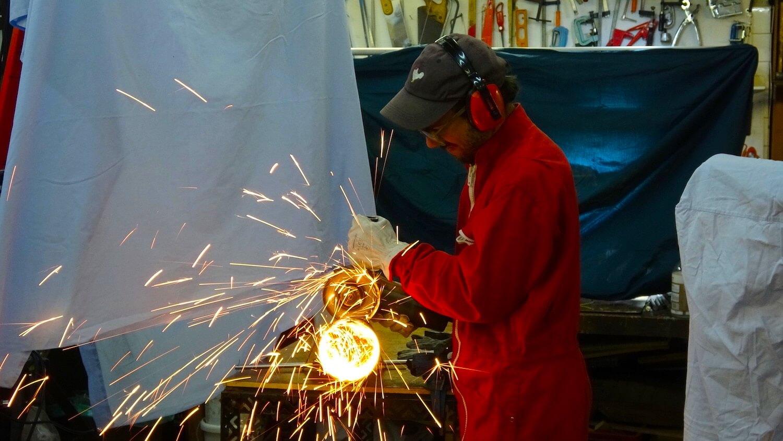 Photographie un homme en tenue rouge et protections découpe un tube avec une meuleuse qui dégage un feu d'artifice d'étincelles