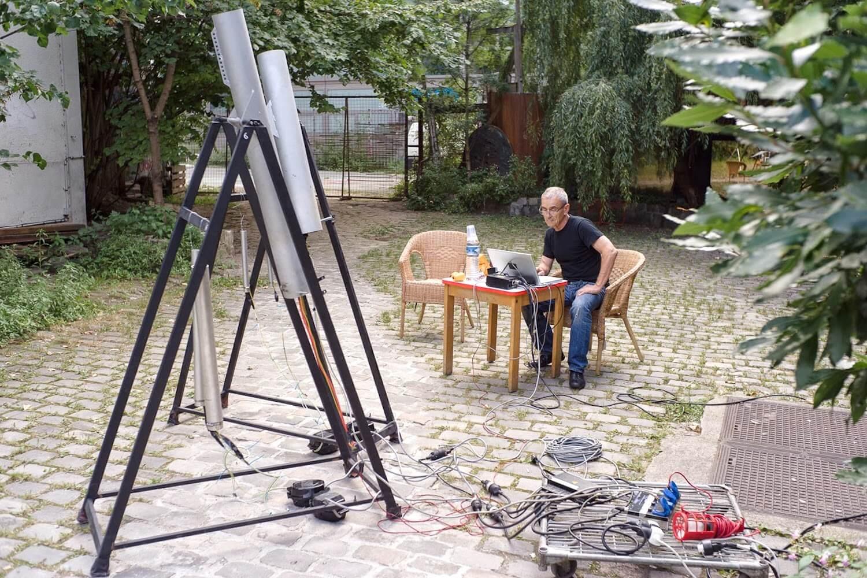 Photographie : une demis douzaine de tubes gris sur supports noirs et un homme assis à une table manipule un ordinateur, dans une cour pavée végétalisée
