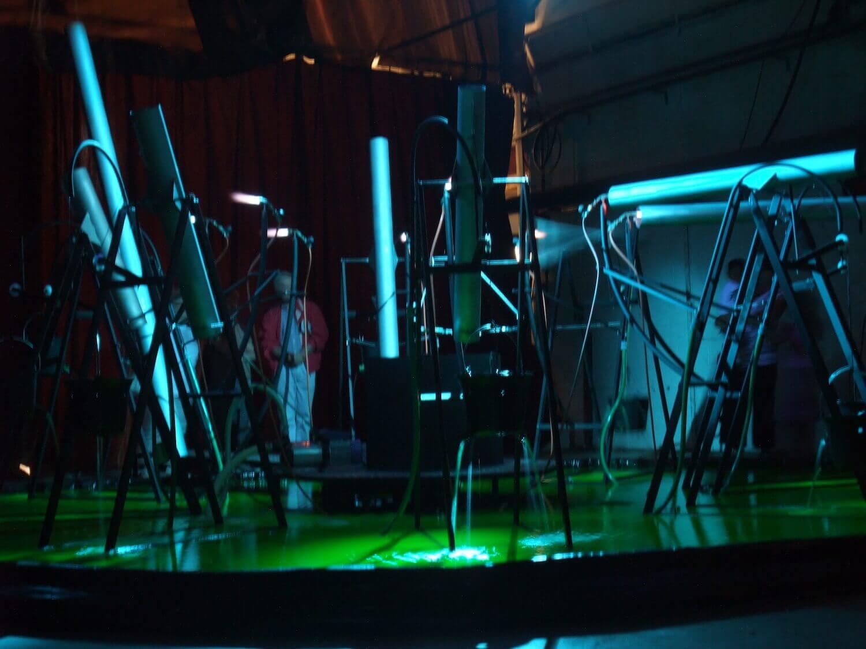 Photographie : public vu à travers une installation de tubes et de bruleurs dans un bassin rempli d'un liquide vert-fluorescent. Lumière bleus dominante.