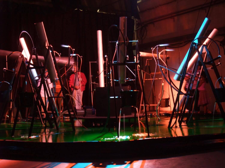 Photographie : public vu à travers une installation de tubes et de bruleurs dans un bassin rempli d'un liquide vert-fluorescent.