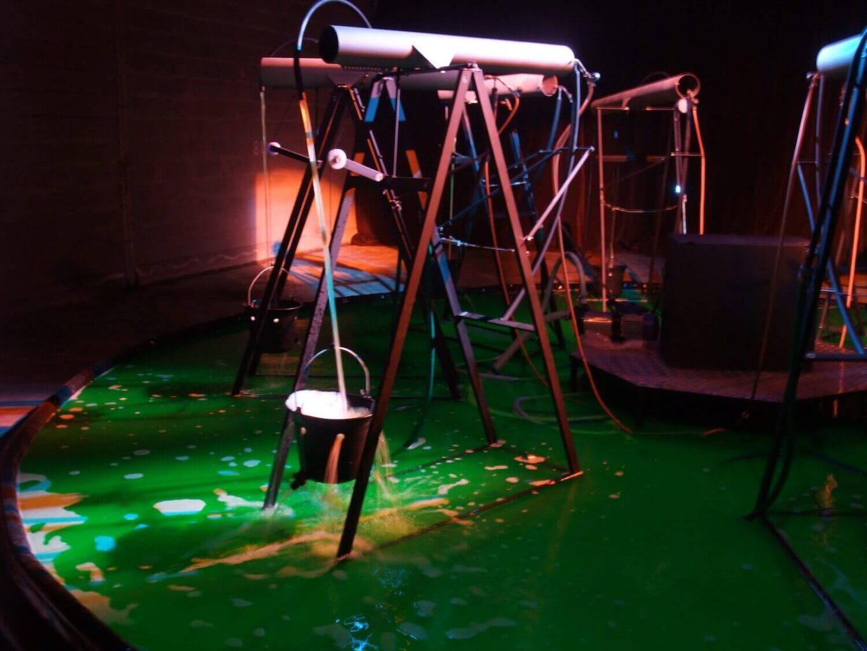 Photographie montrant un tube sur support métallique avec un jet d'eau remplissant un seau percé au dessus d'un bassin d'au verte fluorescente.