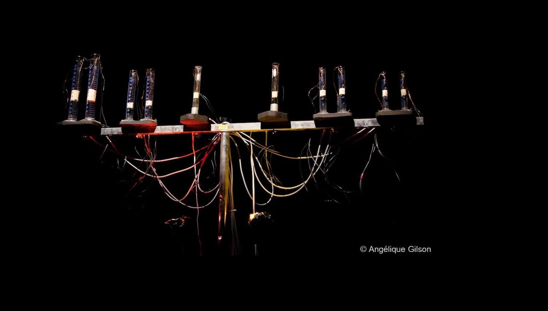 Photographie sur fond noir barre horizontale sur pied supportant 10 tubes en verre avec fils électriques