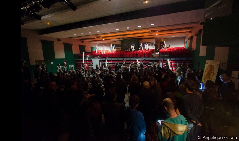Photographie : salle de concert à l'envers, public en premier plan et tubes éclairés au fond sur gradins rouges