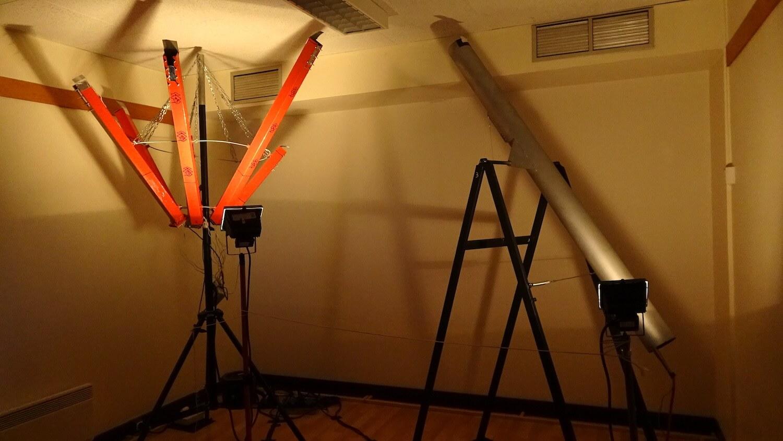 Photographie dans une pièce claire, une ensemble de tubes disposés en pétales de fleur sur la gauche et un long tuyau gris sur la droite.